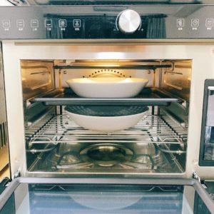將網架放在烘烤爐下層,中層放蒸烤盤,放入兩道菜